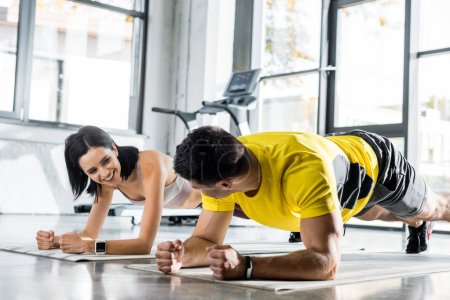 Photo for Sportsman and smiling sportswoman doing plank on fitness mats in sports center - Royalty Free Image