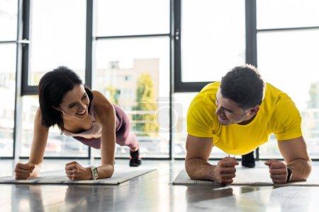 Photo pour Smiling sportsman et sportswoman doing plank on fitness mats in sports center - image libre de droit