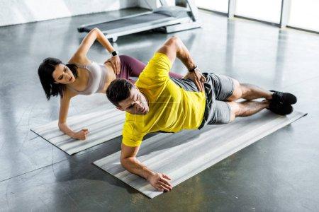 Photo pour Sportif et sportive faisant planche sur tapis de fitness dans le centre sportif - image libre de droit