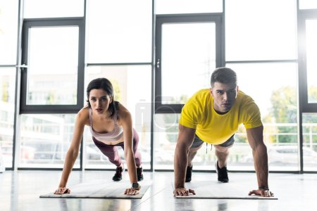 Photo for Sportsman and sportswoman doing plank on fitness mats in sports center - Royalty Free Image
