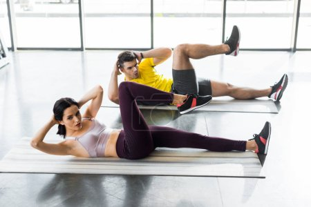 Photo for Sportsman and sportswoman doing crunches on fitness mats in sports center - Royalty Free Image