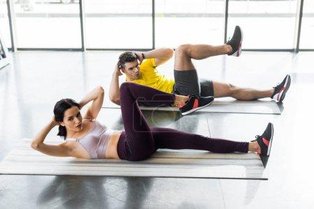 Foto de Deportista y deportista haciendo crujidos en colchonetas de fitness en el centro deportivo - Imagen libre de derechos