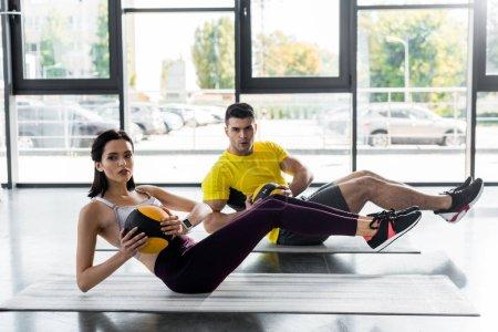 Photo pour Sportif et sportive faisant des croûtes avec des balles sur des tapis de fitness dans un centre sportif - image libre de droit