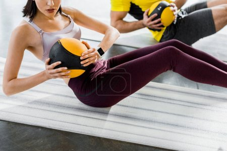 Photo for Cropped view of sportsman and sportswoman doing crunches with balls on fitness mats in sports center - Royalty Free Image