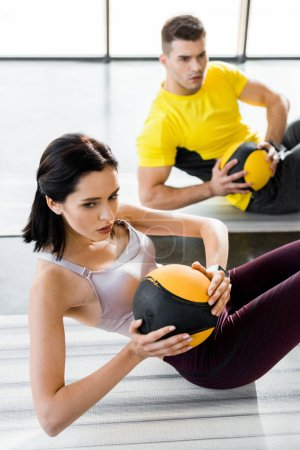 Photo for Sportsman and sportswoman doing crunches with balls on fitness mats in sports center - Royalty Free Image