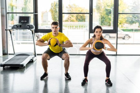 Photo pour Sportsman and sportswoman doing squat with balls in sports center - image libre de droit