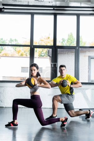 Photo for Sportsman and sportswoman doing lunges with balls in sports center - Royalty Free Image
