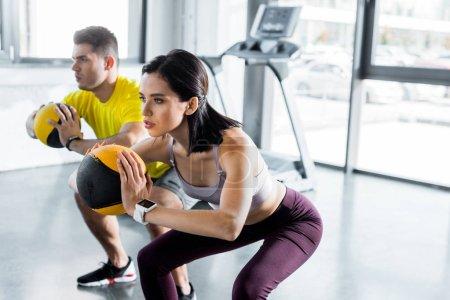 Photo pour Sportif et sportive faisant squat avec des balles dans le centre sportif - image libre de droit