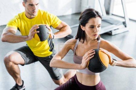 Photo pour Sportif et sportive faisant des fentes avec des balles dans le centre sportif - image libre de droit