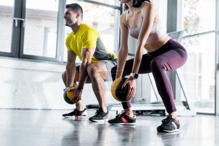 Photo pour Sportsman and sportswoman doing squat with balls in sports center - image libre de droit