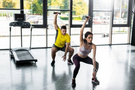Photo pour Sportsman and sportswoman doing squat with dumbbells in sports center - image libre de droit