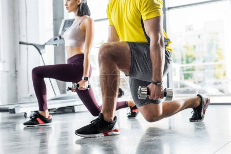 Photo for Cropped view of sportsman and sportswoman doing lunges with dumbbells in sports center - Royalty Free Image