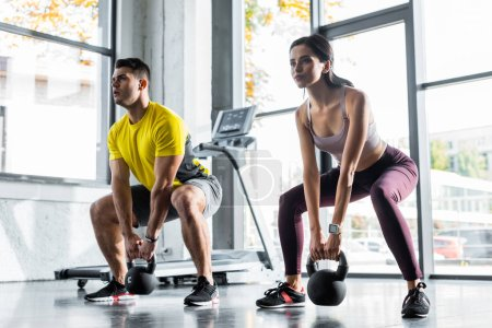 Photo pour Sportsman and sportswoman doing squat with weights in sports center - image libre de droit