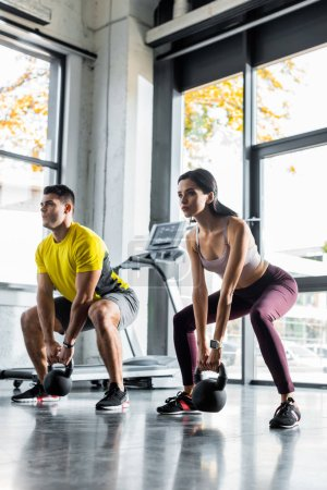 Photo for Sportsman and sportswoman doing squat with weights in sports center - Royalty Free Image