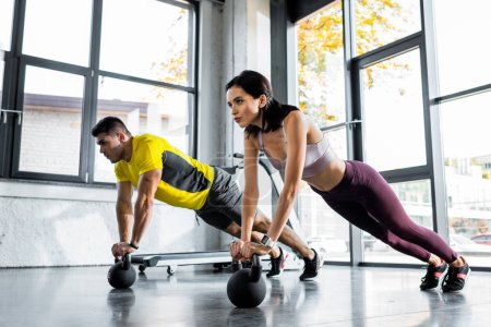 Photo pour Sportif et sportive faisant planche sur les poids dans le centre sportif - image libre de droit