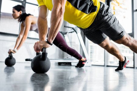 Photo for Cropped view of sportsman and sportswoman doing plank on weights in sports center - Royalty Free Image