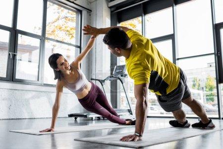 Photo pour Sportif et sportive souriante faisant planche et applaudissant sur des tapis de fitness dans le centre sportif - image libre de droit