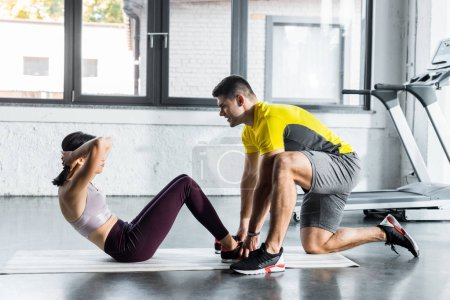 Photo pour Sportswswoman doing crunches and sportsman helping her in sports center - image libre de droit