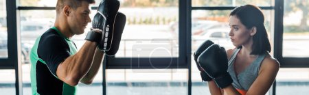 Photo for Panoramic shot of sportswoman in boxing gloves working out with sportsman in sports center - Royalty Free Image