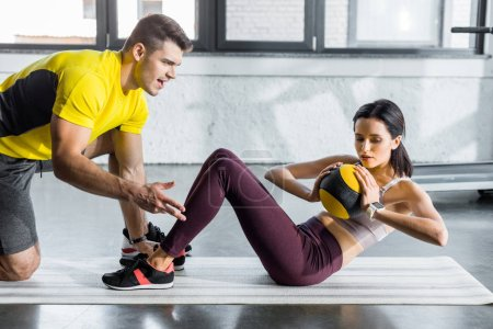 Photo pour Sportswswoman doing crunches with ball and sportsman helping her in sports center - image libre de droit