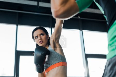 Photo for Sportswoman in boxing gloves working out with sportsman in sports center - Royalty Free Image