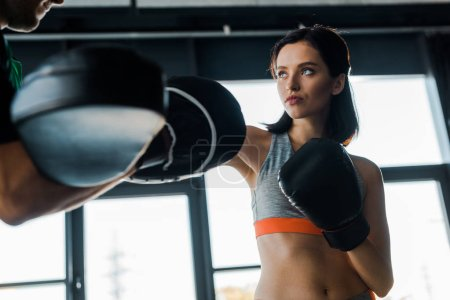 Photo pour Sportswoman in boxing gloves working out with sportsman in sports center - image libre de droit