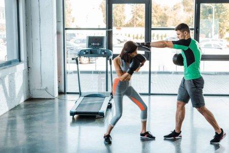 Photo pour Sportive en gants de boxe travaillant avec un sportif dans un centre sportif - image libre de droit