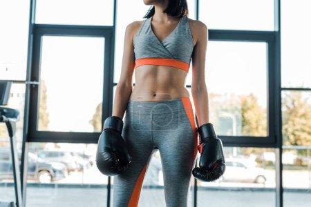 Photo pour Crochet vue de la sportive en gants de boxe dans le centre sportif - image libre de droit