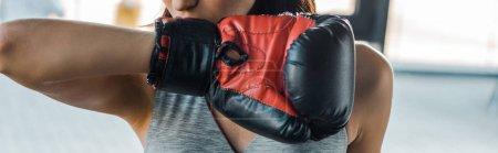 Photo pour Photo panoramique d'une sportive dans un gant de boxe dans un centre sportif - image libre de droit