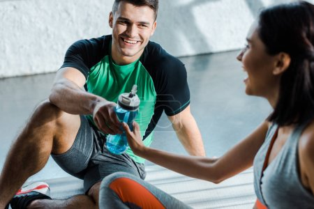 Photo for Smiling sportsman giving sports bottle to sportswoman in sports center - Royalty Free Image