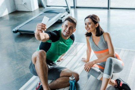 Photo pour Sportsman taking selfie avec smiling sportswoman dans le centre sportif - image libre de droit