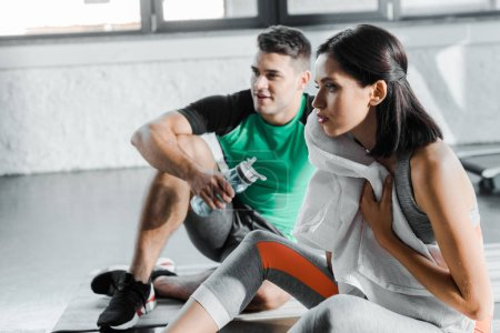 Photo for Sportsman with sports bottle and sportswoman with towel sitting in sports center - Royalty Free Image