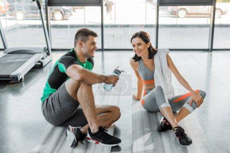 Photo pour Sportif avec bouteille de sport et sportif avec serviette parlant au centre sportif - image libre de droit