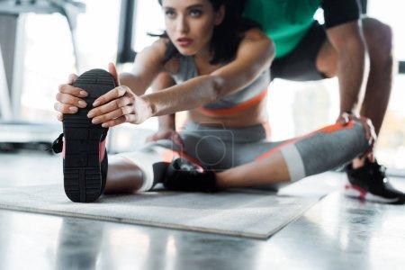 Photo pour Foyer sélectif de femme sportive étirement et sportif l'aidant dans le centre sportif - image libre de droit