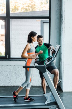 Photo for Sportswoman running on treadmill and sportsman pointing with finger - Royalty Free Image