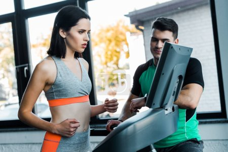 Photo for Sportswoman running on treadmill and sportsman standing near in sports center - Royalty Free Image