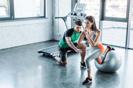 Photo pour Sportive faisant des poussées sur le ballon de remise en forme et sportif l'aider - image libre de droit