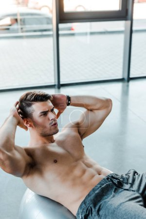 Photo for Handsome and shirtless sportsman doing crunches in sports center - Royalty Free Image