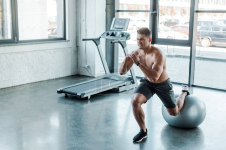 Photo for Handsome sportsman doing lunges on fitness ball in sports center - Royalty Free Image