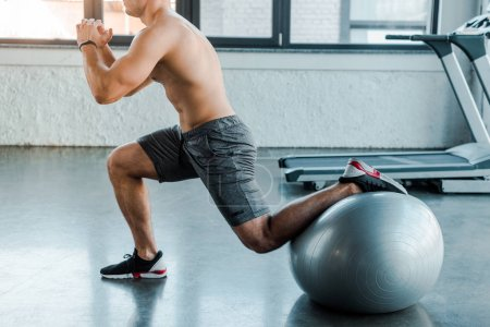Photo for Cropped view of sportsman doing lunges on fitness ball in sports center - Royalty Free Image