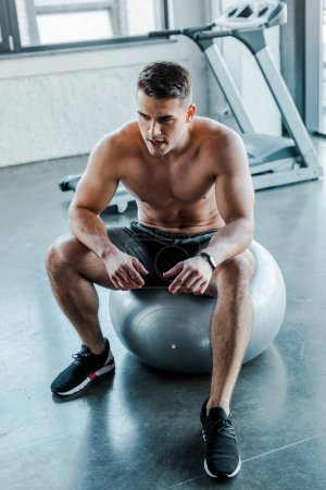 Photo for Handsome sportsman sitting on fitness ball in sports center - Royalty Free Image