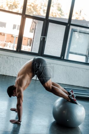 Photo for Handsome sportsman working out on fitness ball in sports center - Royalty Free Image