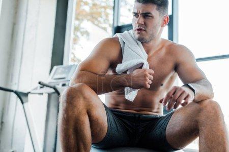 schöner Sportler sitzt und hält Handtuch im Sportzentrum