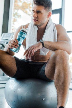 Photo pour Sportif assis sur le ballon de remise en forme et tenant bouteille de sport dans le centre sportif - image libre de droit