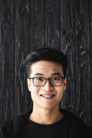 Photo for Smiling asian man in glasses looking at camera on wooden background - Royalty Free Image