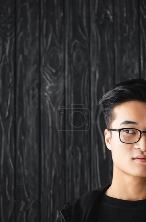 cropped view of asian man in glasses looking away on wooden background