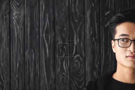 Photo pour Crocheté vue d'un homme d'Asie en lunettes regardant loin sur fond de bois - image libre de droit
