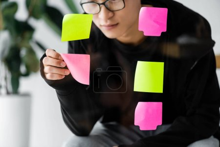 Photo for Asian seo manager in glasses taking sticky note from glass - Royalty Free Image