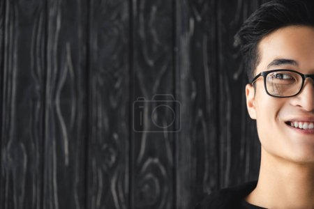cropped view of smiling asian man in glasses looking away on wooden background