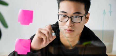 Photo for Panoramic shot of asian seo manager in glasses painting arrow on glass - Royalty Free Image